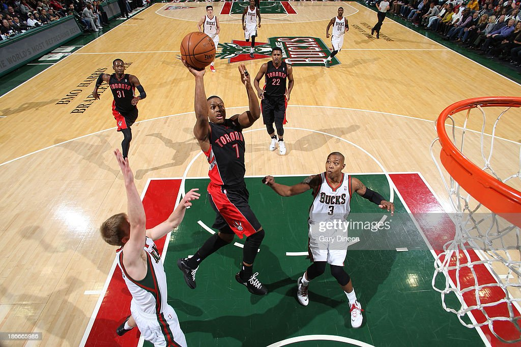 <a gi-track='captionPersonalityLinkClicked' href=/galleries/search?phrase=Kyle+Lowry&family=editorial&specificpeople=714625 ng-click='$event.stopPropagation()'>Kyle Lowry</a> #7 of the Toronto Raptors shoots against (L-R) <a gi-track='captionPersonalityLinkClicked' href=/galleries/search?phrase=Nate+Wolters&family=editorial&specificpeople=9023990 ng-click='$event.stopPropagation()'>Nate Wolters</a> #6 and <a gi-track='captionPersonalityLinkClicked' href=/galleries/search?phrase=Caron+Butler&family=editorial&specificpeople=201744 ng-click='$event.stopPropagation()'>Caron Butler</a> #3 of the Milwaukee Bucks on November 2, 2013 at the BMO Harris Bradley Center in Milwaukee, Wisconsin.