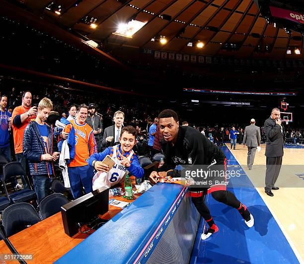 Kyle Lowry of the Toronto Raptors takes a photo with a fan during the game against the New York Knicks on February 22 2016 at Madison Square Garden...