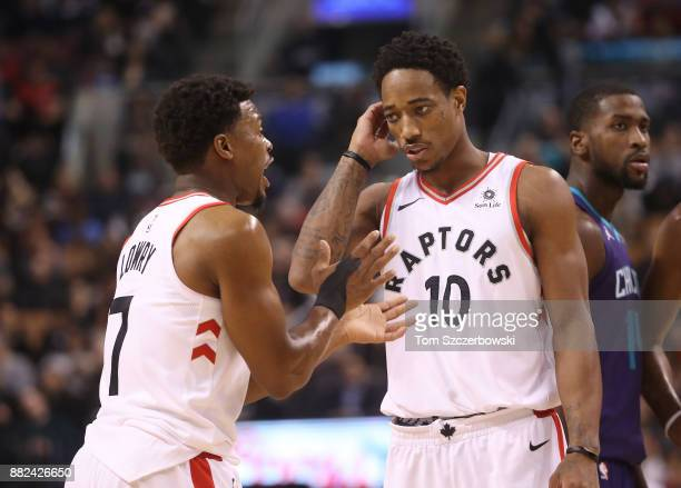Kyle Lowry of the Toronto Raptors talks to DeMar DeRozan against the Charlotte Hornets during NBA game action at Air Canada Centre on November 29...