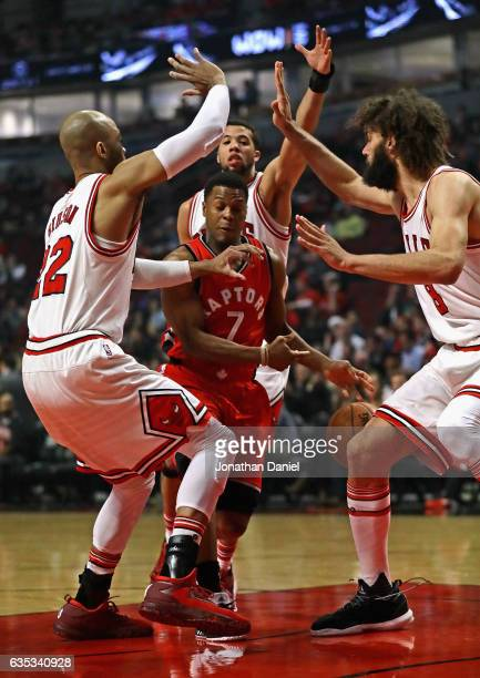 Kyle Lowry of the Toronto Raptors tries to drive between Taj Gibson Michael CarterWilliams and Robin Lopez of the Chicago Bulls at the United Center...