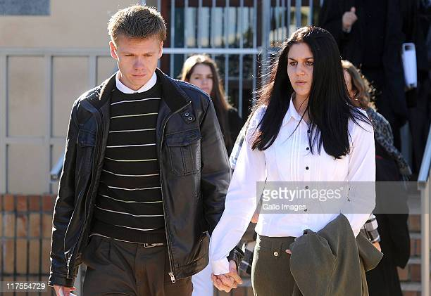 Kyle MacDonald and his girlfriend Jeanine van der Merwe hold hands as they walk outside the Strand Regional court on June 27 2011 in Cape Town South...
