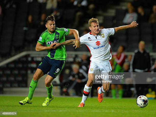 Kyle McFadzean of MK Dons is tackled by Jay Rodriguez of Southampton during the Capital One Cup third round match between MK Dons and Southampton at...