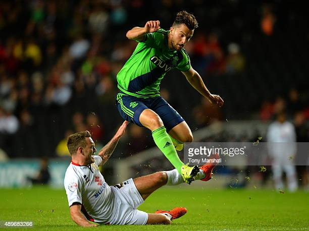 Kyle McFadzean of MK Dons tackles Jay Rodriguez of Southampton during the Capital One Cup third round match between MK Dons and Southampton at...