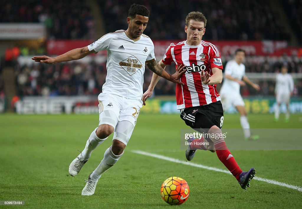 Kyle Naughton of Swansea City and Steven Davis of Southampton compete for the ball during the Barclays Premier League match between Swansea City and Southampton at Liberty Stadium on February 13, 2016 in Swansea, Wales.