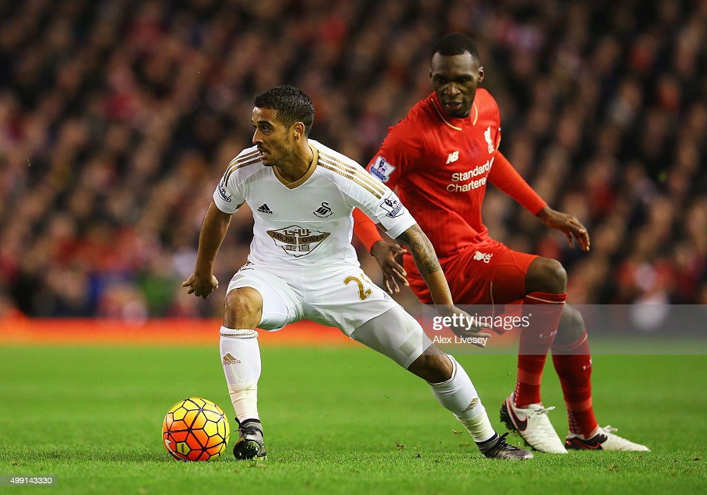 Kyle Naughton of Swansea City evades Christian Benteke of Liverpool during the Barclays Premier League match between Liverpool and Swansea City at Anfield on November 29, 2015 in Liverpool, England.