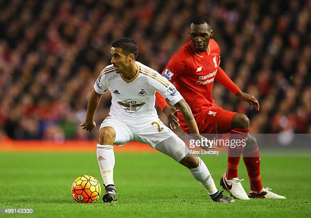 Kyle Naughton of Swansea City evades Christian Benteke of Liverpool during the Barclays Premier League match between Liverpool and Swansea City at...
