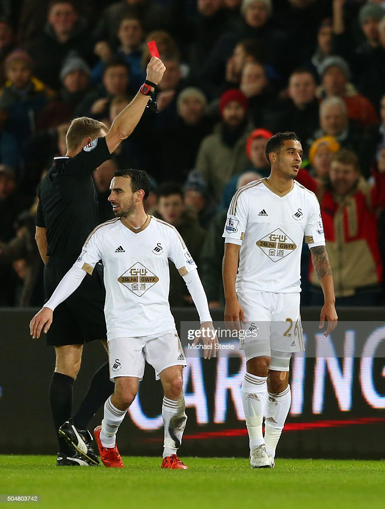 Kyle Naughton (R) of Swansea City is shown a red card by referee Graham Scott (L) during the Barclays Premier League match between Swansea City and Sunderland at the Liberty Stadium on January 13, 2016 in Swansea, Wales.