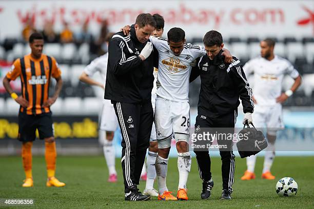 Kyle Naughton of Swansea City limps away after being challenged by David Meyler of Hull City during the Barclays Premier League match between Swansea...