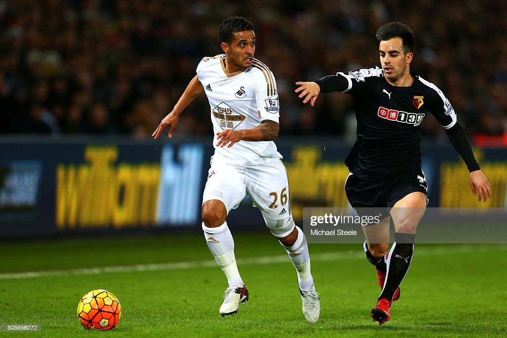 Kyle Naughton of Swansea City runs with the ball under pressure from Jose Manuel Jurado of Watford during the Barclays Premier League match between Swansea City and Watford at Liberty Stadium on January 18, 2016 in Swansea, Wales.