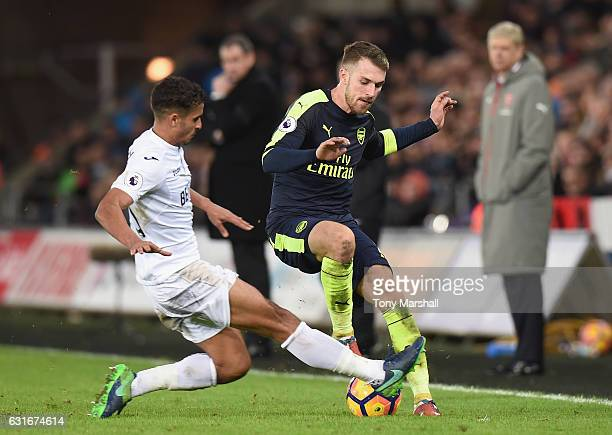 Kyle Naughton of Swansea City tackles Aaron Ramsey of Arsenal during the Premier League match between Swansea City and Arsenal at Liberty Stadium on...