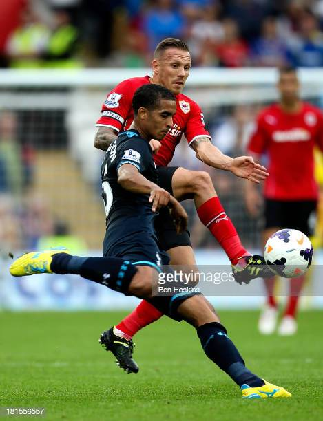 Kyle Naughton of Tottenham clears his lines ahead of Craig Bellamy of Cardiff during the Barclays Premier League match between Cardiff City and...