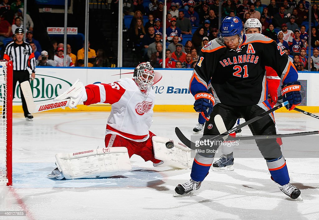 <a gi-track='captionPersonalityLinkClicked' href=/galleries/search?phrase=Kyle+Okposo&family=editorial&specificpeople=540469 ng-click='$event.stopPropagation()'>Kyle Okposo</a> #21 of the New York Islanders and <a gi-track='captionPersonalityLinkClicked' href=/galleries/search?phrase=Jonas+Gustavsson&family=editorial&specificpeople=886789 ng-click='$event.stopPropagation()'>Jonas Gustavsson</a> #50 of the Detroit Red Wings keep their eye on the puck at Nassau Veterans Memorial Coliseum on November 16, 2013 in Uniondale, New York.