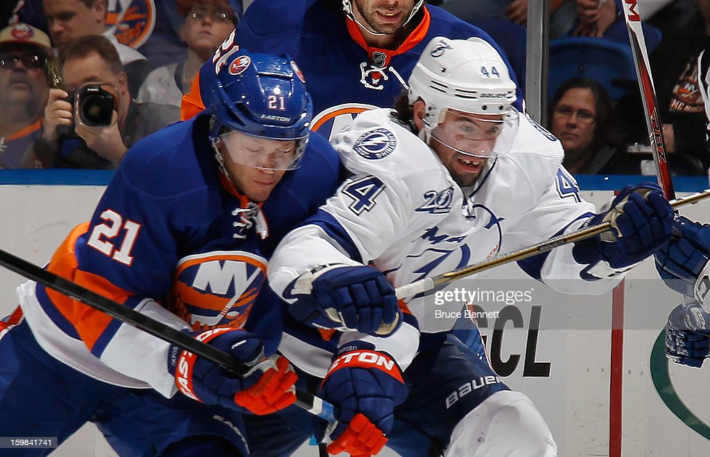Kyle Okposo #21 of the New York Islanders battles with Nate Thompson #44 of the Tampa Bay Lightning at the Nassau Veterans Memorial Coliseum on January 21, 2013 in Uniondale, New York. The Islanders defeated the Lightning 4-3.