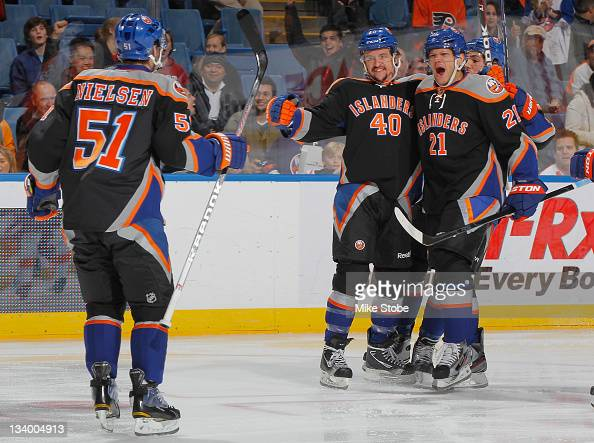 Kyle Okposo of the New York Islanders celebrates his first goal of the 20112012 season with teammates Michael Grabner and Frans Nielsen during the...