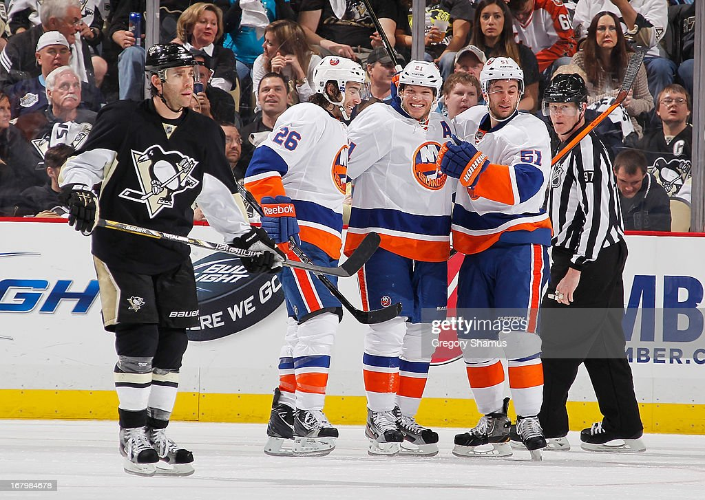<a gi-track='captionPersonalityLinkClicked' href=/galleries/search?phrase=Kyle+Okposo&family=editorial&specificpeople=540469 ng-click='$event.stopPropagation()'>Kyle Okposo</a> #21 of the New York Islanders celebrates his goal with <a gi-track='captionPersonalityLinkClicked' href=/galleries/search?phrase=Matt+Moulson&family=editorial&specificpeople=3365493 ng-click='$event.stopPropagation()'>Matt Moulson</a> #26 and <a gi-track='captionPersonalityLinkClicked' href=/galleries/search?phrase=Frans+Nielsen&family=editorial&specificpeople=634894 ng-click='$event.stopPropagation()'>Frans Nielsen</a> #51 as <a gi-track='captionPersonalityLinkClicked' href=/galleries/search?phrase=Pascal+Dupuis&family=editorial&specificpeople=208971 ng-click='$event.stopPropagation()'>Pascal Dupuis</a> #9 of the Pittsburgh Penguins skates by in Game Two of the Eastern Conference Quarterfinals during the 2013 NHL Stanley Cup Playoffs at Consol Energy Center on May 3, 2013 in Pittsburgh, Pennsylvania. New York won the game 4-3.
