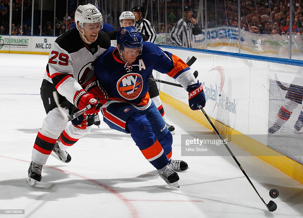 Kyle Okposo #21 of the New York Islanders controls the puck in front of Mark Fayne #29 of the New Jersey Devils at Nassau Veterans Memorial Coliseum on January 19, 2013 in Uniondale, New York. The Devils defeated the Islanders 2-1.