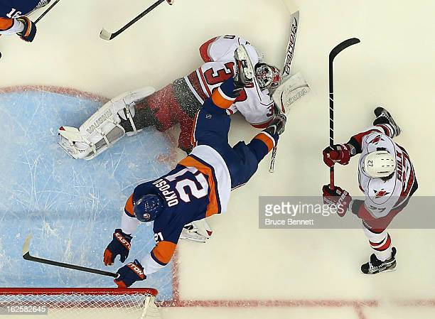 Kyle Okposo of the New York Islanders flies over Cam Ward of the Carolina Hurricanes at the Nassau Veterans Memorial Coliseum on February 24 2013 in...