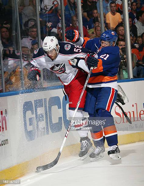 Kyle Okposo of the New York Islanders hits David Savard of the Columbus Blue Jackets into the boards at the Nassau Veterans Memorial Coliseum on...