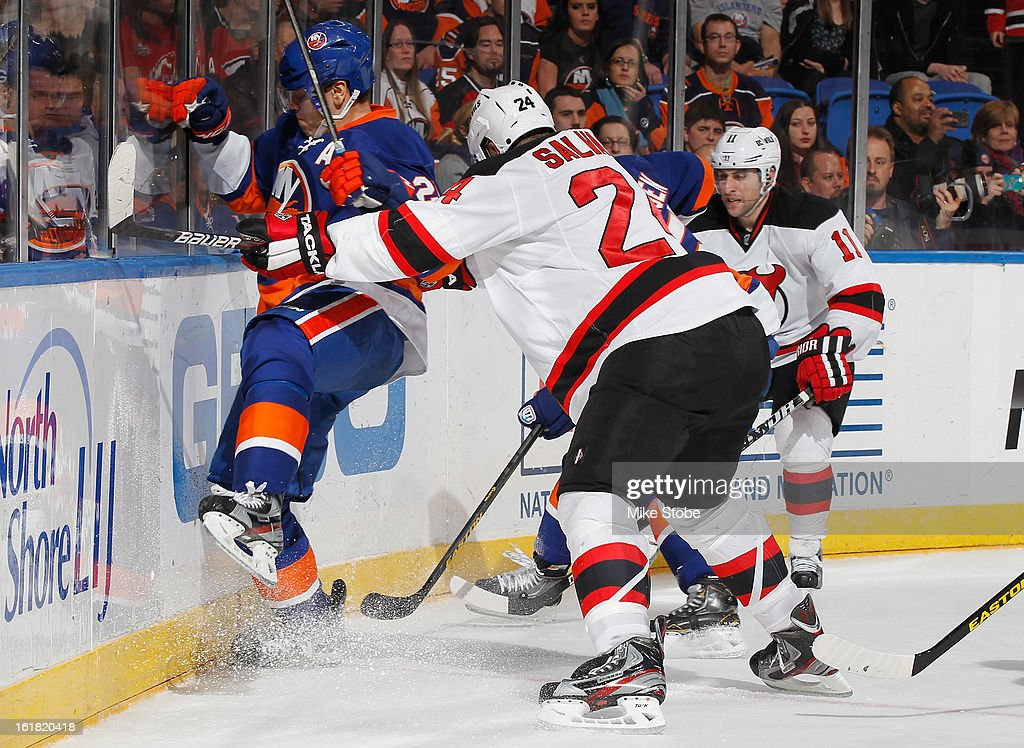 <a gi-track='captionPersonalityLinkClicked' href=/galleries/search?phrase=Kyle+Okposo&family=editorial&specificpeople=540469 ng-click='$event.stopPropagation()'>Kyle Okposo</a> #21 of the New York Islanders is checked into the boards by <a gi-track='captionPersonalityLinkClicked' href=/galleries/search?phrase=Bryce+Salvador&family=editorial&specificpeople=208746 ng-click='$event.stopPropagation()'>Bryce Salvador</a> #24 of the New Jersey Devils at Nassau Veterans Memorial Coliseum on February 16, 2013 in Uniondale, New York. The Islanders defeated the Devils 5-1.