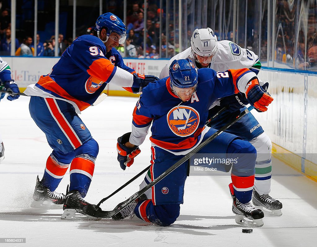 <a gi-track='captionPersonalityLinkClicked' href=/galleries/search?phrase=Kyle+Okposo&family=editorial&specificpeople=540469 ng-click='$event.stopPropagation()'>Kyle Okposo</a> #21 of the New York Islanders is knocked to the ice in front of teammate <a gi-track='captionPersonalityLinkClicked' href=/galleries/search?phrase=John+Tavares&family=editorial&specificpeople=601791 ng-click='$event.stopPropagation()'>John Tavares</a> #91 and <a gi-track='captionPersonalityLinkClicked' href=/galleries/search?phrase=Ryan+Kesler&family=editorial&specificpeople=206915 ng-click='$event.stopPropagation()'>Ryan Kesler</a> #17 of the Vancouver Canucks at Nassau Veterans Memorial Coliseum on October 22, 2013 in Uniondale, New York. The Canucks defeated the Islanders 5-4 in overtime.