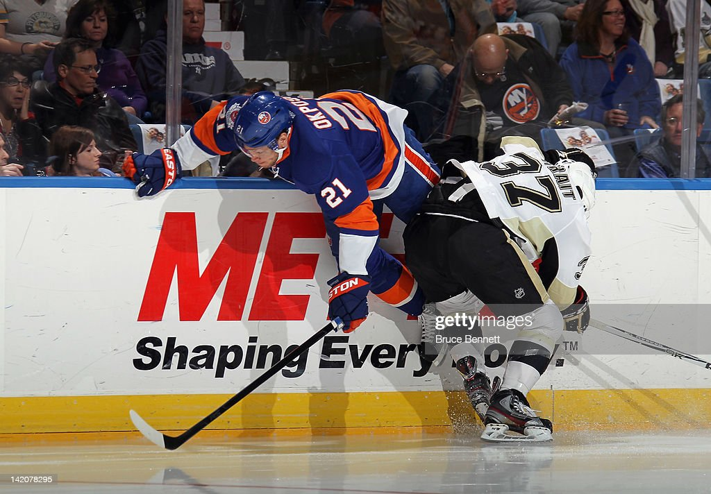 Kyle Okposo of the New York Islanders is tripped up by Brian Strait of the Pittsburgh Penguins at the Nassau Veterans Memorial Coliseum on March 29...