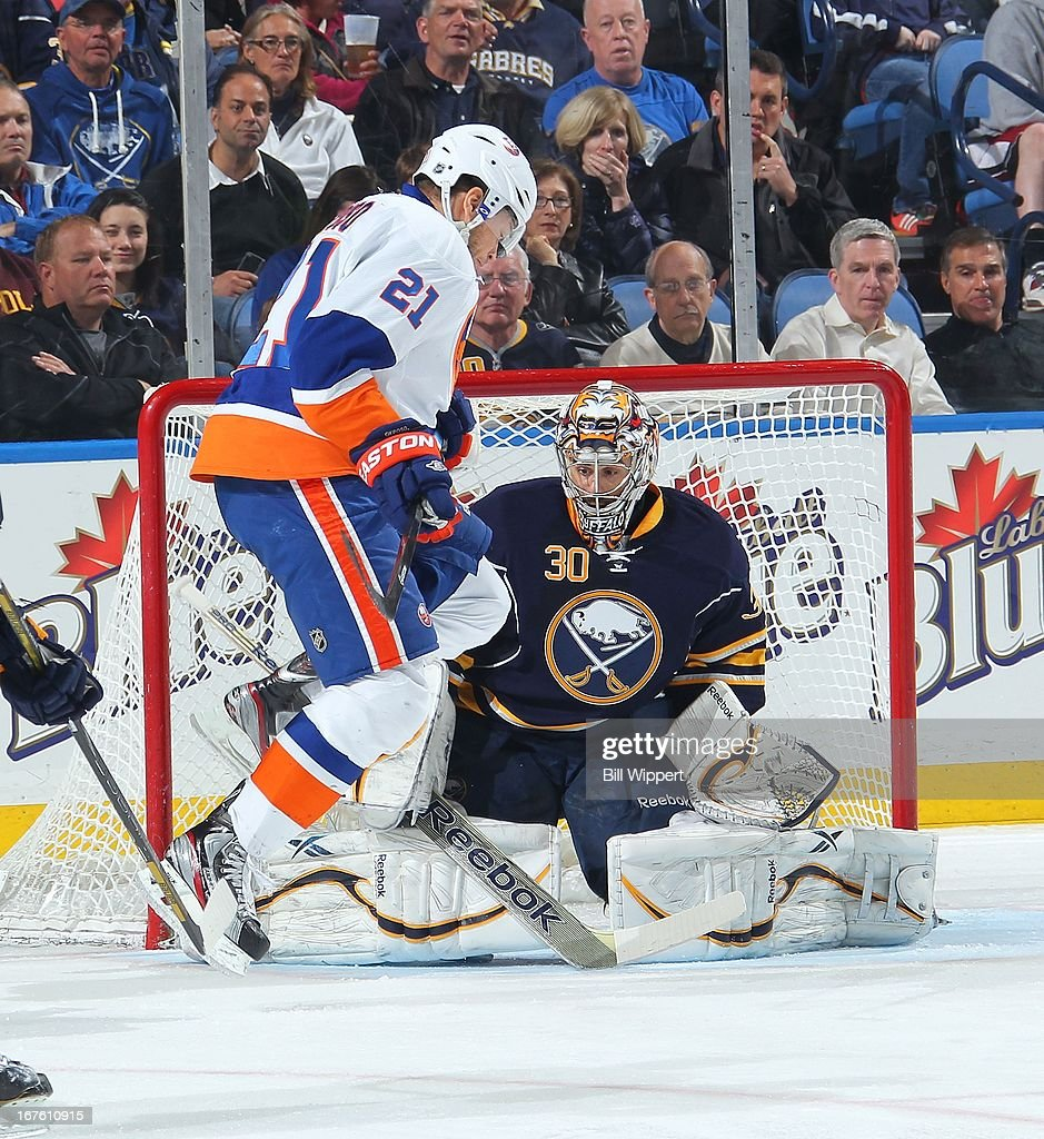Kyle Okposo #21 of the New York Islanders jumps while screening Ryan Miller #30 of the Buffalo Sabres on April 26, 2013 at the First Niagara Center in Buffalo, New York.