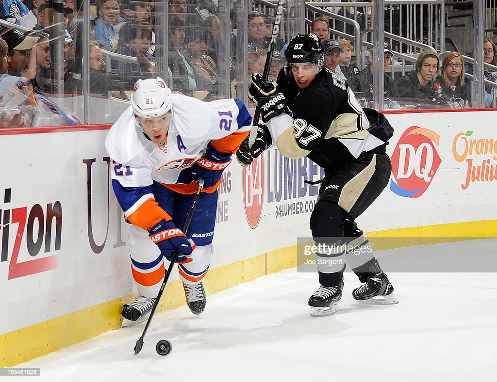 Kyle Okposo #21 of the New York Islanders moves the puck in front of Sidney Crosby #87 of the Pittsburgh Penguins on March 10, 2013 at Consol Energy Center in Pittsburgh, Pennsylvania.
