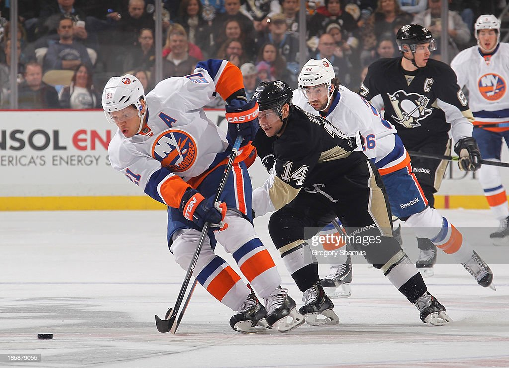 Kyle Okposo of the New York Islanders moves the puck up ice in front of Chris Kunitz of the Pittsburgh Penguins on October 25 2013 at Consol Energy...