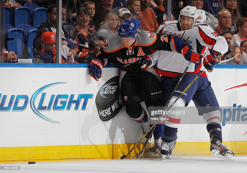 Kyle Okposo #21 of the New York Islanders pursues the puck against Eric Fehr #16 of the Washington Capitals at Nassau Veterans Memorial Coliseum on March 9, 2013 in Uniondale, New York.
