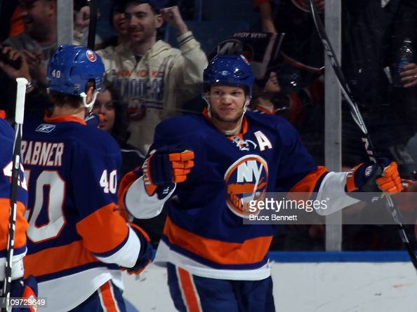 Kyle Okposo of the New York Islanders scores at 1837 of the first period against the Minnesota Wild and is joined by Michael Grabner at the Nassau...