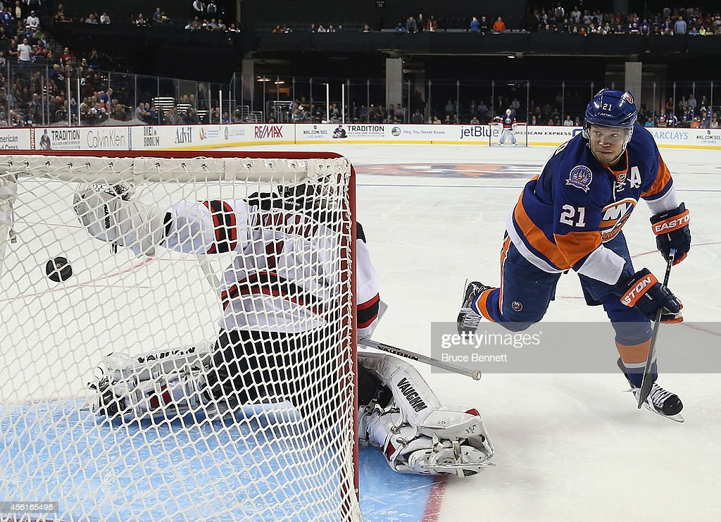 Kyle Okposo of the New York Islanders scores the shootout goal against Keith Kinkaid of the New Jersey Devils at the Barclays Center on September 26...