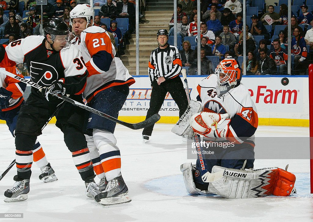 Kyle Okposo of the New York Islanders ties up Darroll Powe of the Philadelphia Flyers as goaltender Martin Biron of the Islanders makes the save on...