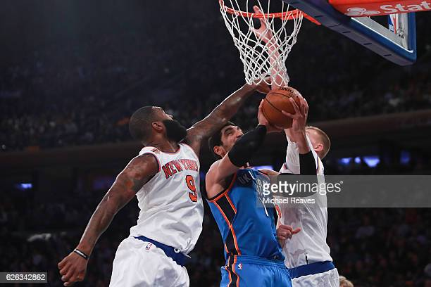 Kyle O'Quinn and Kristaps Porzingis of the New York Knicks defend a shot by Enes Kanter of the Oklahoma City Thunder during the first half at Madison...