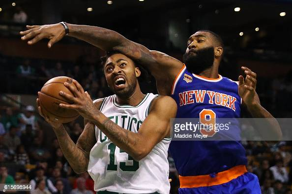 Kyle O'Quinn of the New York Knicks defends James Young of the Boston Celtics during the third quarter at TD Garden on October 17 2016 in Boston...