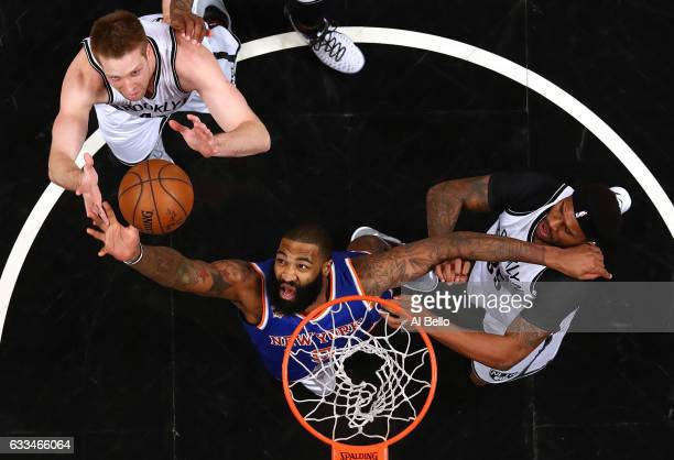 Kyle O'Quinn of the New York Knicks rebounds against Trevor Booker and Justin Hamilton of the Brooklyn Nets during their game at the Barclays Center...