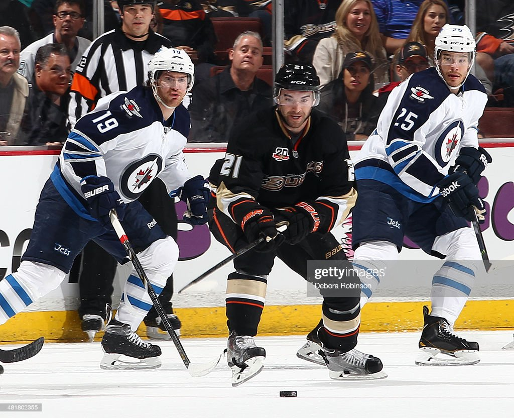 <a gi-track='captionPersonalityLinkClicked' href=/galleries/search?phrase=Kyle+Palmieri&family=editorial&specificpeople=4783296 ng-click='$event.stopPropagation()'>Kyle Palmieri</a> #21 of the Anaheim Ducks battles for the puck against Jim Slater #19 and <a gi-track='captionPersonalityLinkClicked' href=/galleries/search?phrase=Zach+Redmond&family=editorial&specificpeople=8234699 ng-click='$event.stopPropagation()'>Zach Redmond</a> #25 of the Winnipeg Jets on March 31, 2014 at Honda Center in Anaheim, California.