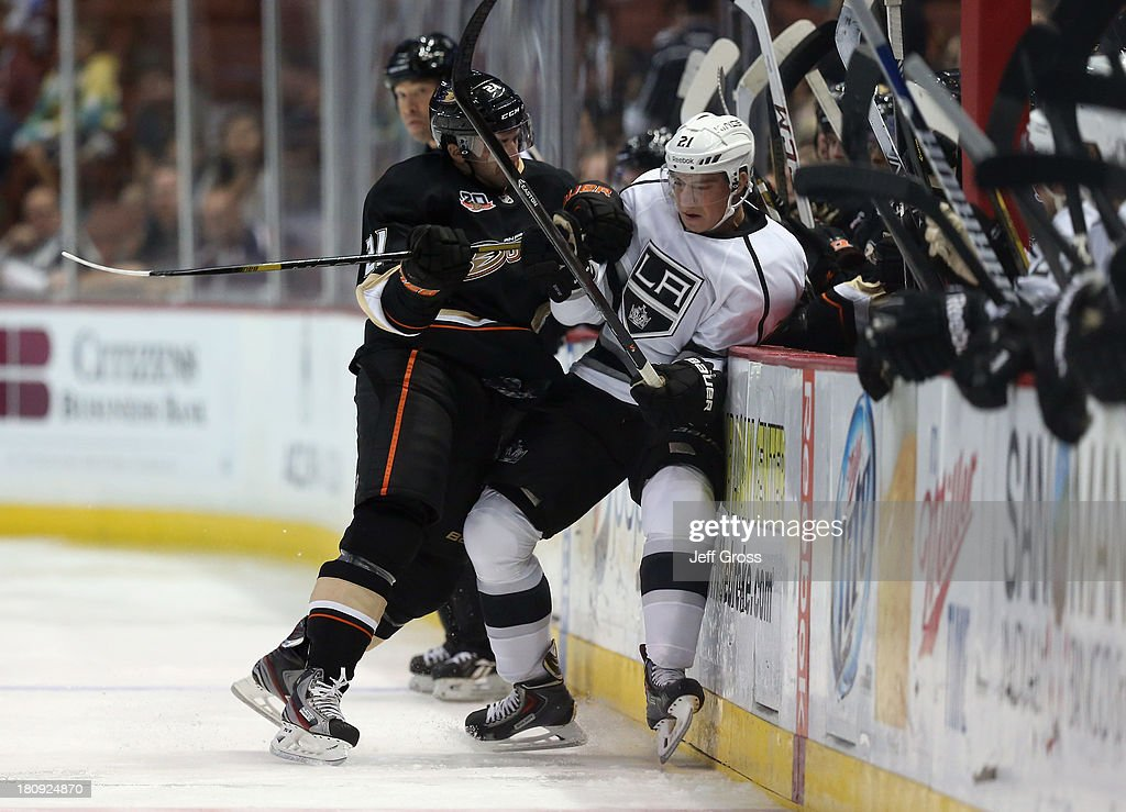 <a gi-track='captionPersonalityLinkClicked' href=/galleries/search?phrase=Kyle+Palmieri&family=editorial&specificpeople=4783296 ng-click='$event.stopPropagation()'>Kyle Palmieri</a> #21 of the Anaheim Ducks checks <a gi-track='captionPersonalityLinkClicked' href=/galleries/search?phrase=Matt+Frattin&family=editorial&specificpeople=5648435 ng-click='$event.stopPropagation()'>Matt Frattin</a> #21 of the Los Angeles Kings into the boards in the second period at Honda Center on September 17, 2013 in Anaheim, California. The Kings defeated the Ducks 6-0.