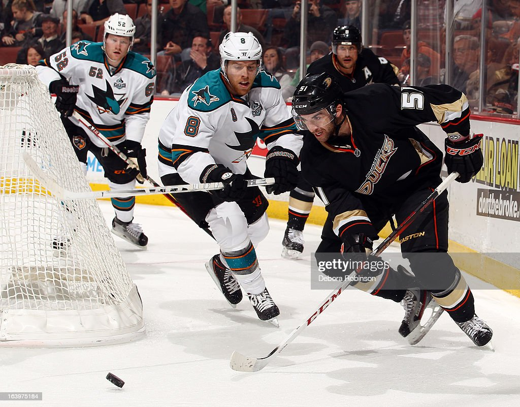 Kyle Palmieri #51 of the Anaheim Ducks handles the puck against Matt Irwin #52 and Joe Pavelski #8 of the San Jose Sharks on March 18, 2013 at Honda Center in Anaheim, California.