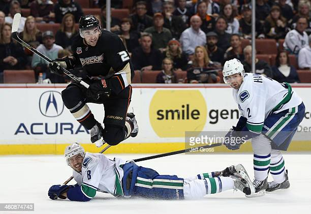 Kyle Palmieri of the Anaheim Ducks jumps to avoid Chris Tanev of the Vancouver Canucks as Dan Hamhuis of the Canucks pursues the play in the third...