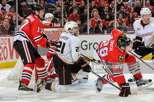 Kyle Palmieri of the Anaheim Ducks watches for the puck in between Sheldon Brookbank and Ben Smith of the Chicago Blackhawks as teammate David...