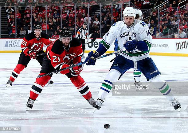 Kyle Palmieri of the New Jersey Devils and Erik Gudbranson of the Vancouver Canucks fight for the puck in the second period on December 6 2016 at...