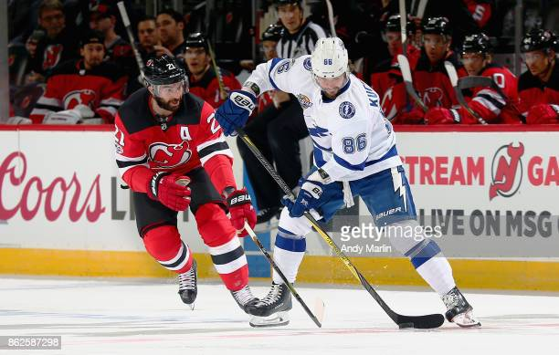 Kyle Palmieri of the New Jersey Devils and Nikita Kucherov of the Tampa Bay Lightning battle for a loose puck during the game at Prudential Center on...