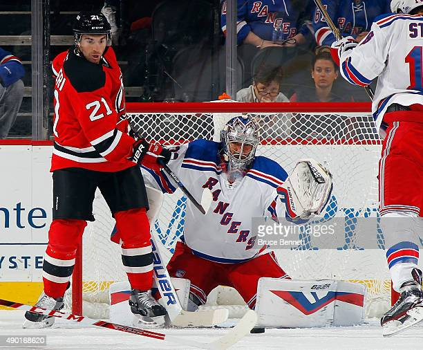 Kyle Palmieri of the New Jersey Devils attempts to deflect a shot against Henrik Lundqvist of the New York Rangers during the first period during a...