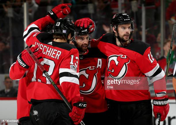 Kyle Palmieri of the New Jersey Devils is congratulated by teammates Will ButcherNico Hischier and Drew Stafford after Palmieri scored a goal in the...