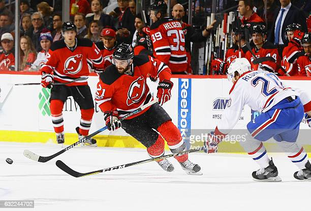 Kyle Palmieri of the New Jersey Devils plays the puck while being defended by Zach Redmond of the Montreal Canadiens during the game at Prudential...