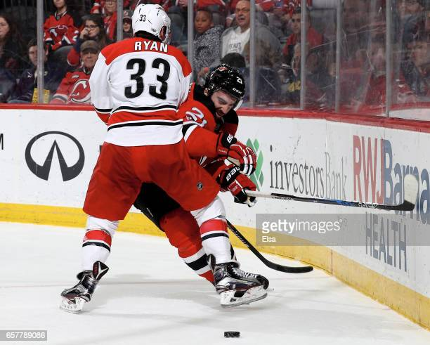 Kyle Palmieri of the New Jersey Devils tries to get past Derek Ryan of the Carolina Hurricanes in the second period on March 25 2017 at Prudential...