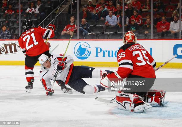 Kyle Palmieri of the New Jersey Devils trips up Nicklas Backstrom of the Washington Capitals during the first period as Cory Schneider watches at the...