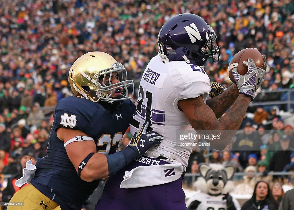 Kyle Prater of the Northwestern Wildcats catches a touchdown pass in front of Drue Tranquill of the Notre Dame Fighting Irish at Notre Dame Stadium...