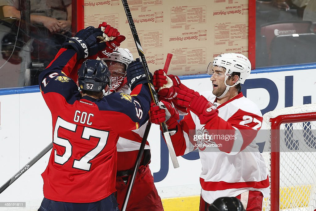 Kyle Quincey and Daniel Alfredsson of the Detroit Red Wings battle next to the net with Marcel Goc of the Florida Panthers at the BBT Center on...