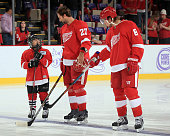 Kyle Quincey and Justin Abdelkader of the Detroit Red Wings greet youth player of the game and brain cancer survivor Anthony Salah on 'Hockey Fights...